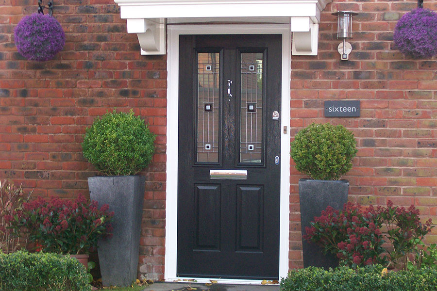 Black composite door with decorative glazing