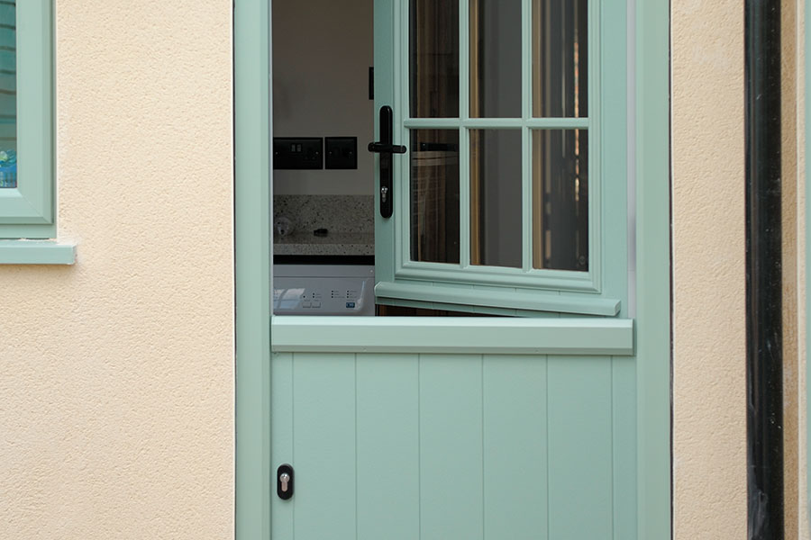 Green traditional style stable door with astragal bars