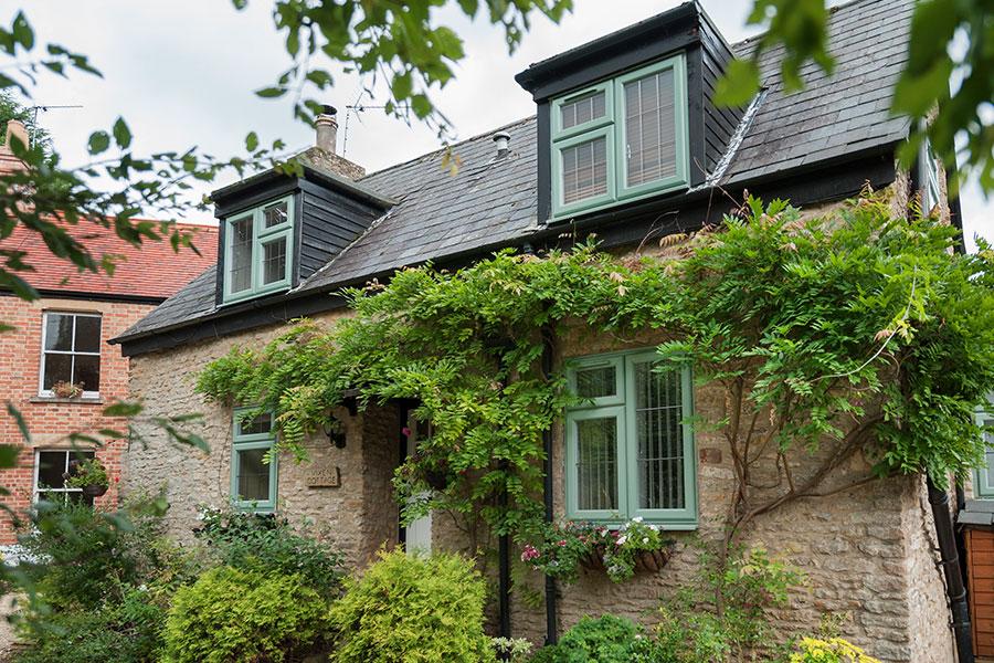 Green casement uPVC window on traditional style property