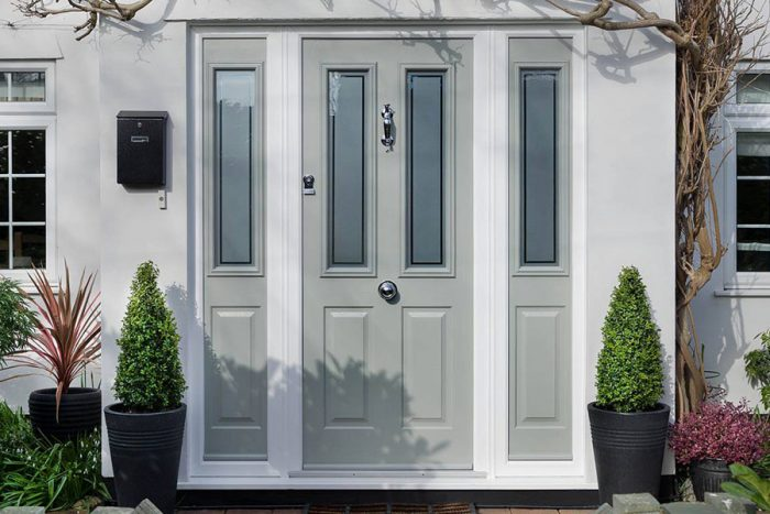 Light grey composite door with glazed panels and sidelights