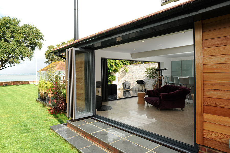 Wide span bifold door opening onto a patio area - bifold doors