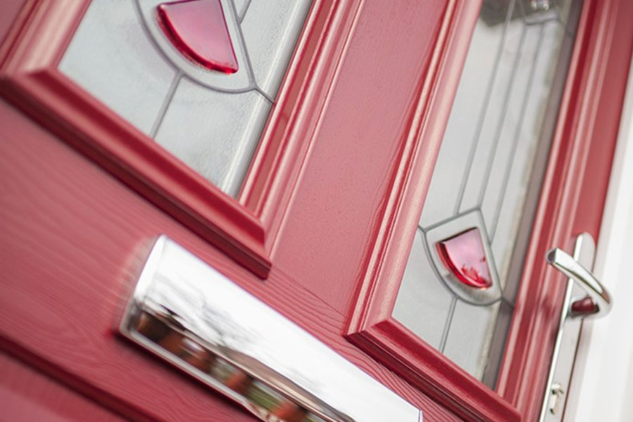 Red composite door with decorative glazing panes and chrome furniture