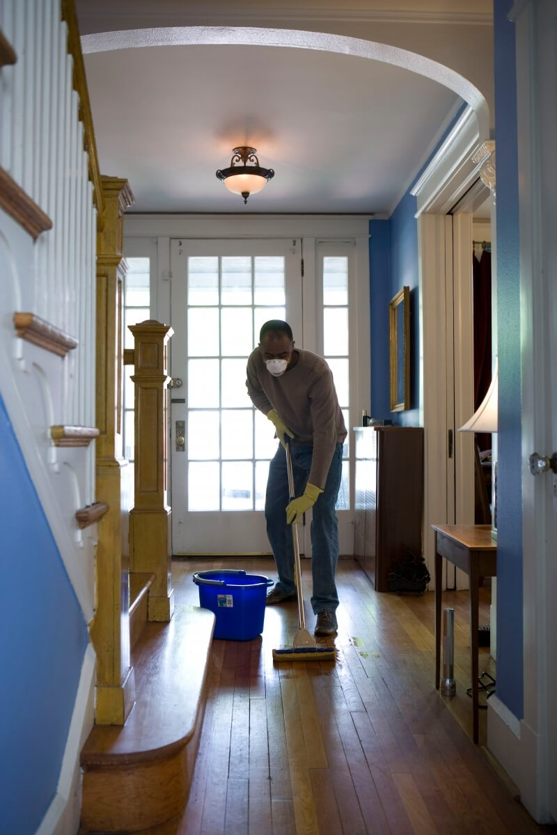 hallway with man cleaning floor